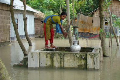 Woman using flood resilient tube well in Bangladesh