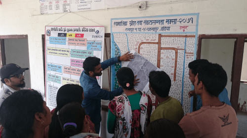Practical Action Nepal, the Center for Social Development and Research and community members discuss the transfer of community maps to online maps © Wei Liu | IIASA