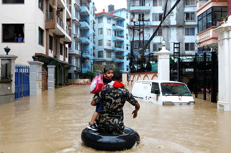 Nepali army carrying a child walks along the flooded colony in Kathmandu, on Friday, July 12, 2019. (Source: The Himalayan Times)