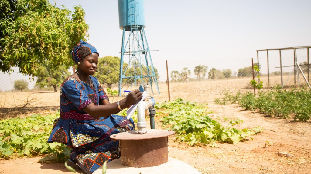 Fatimata Coulibaly and Awa Dembélé, members of the Benkadi women's group, using an electric probe to measure the water level inside a well inside the market garden, Kakounouso, Samabogo, Mali. WaterAid/ Basile Ouedraogo