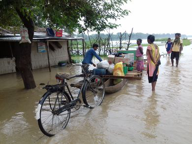 Community members using boats to move grains to safety during flood.