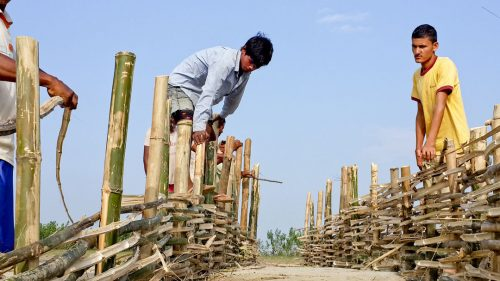 Men building low cost flood mitigation structure using bamboo. Photo by Mercy Corps from the The Managing Risks through Economic Development (M-RED) program in Nepal.